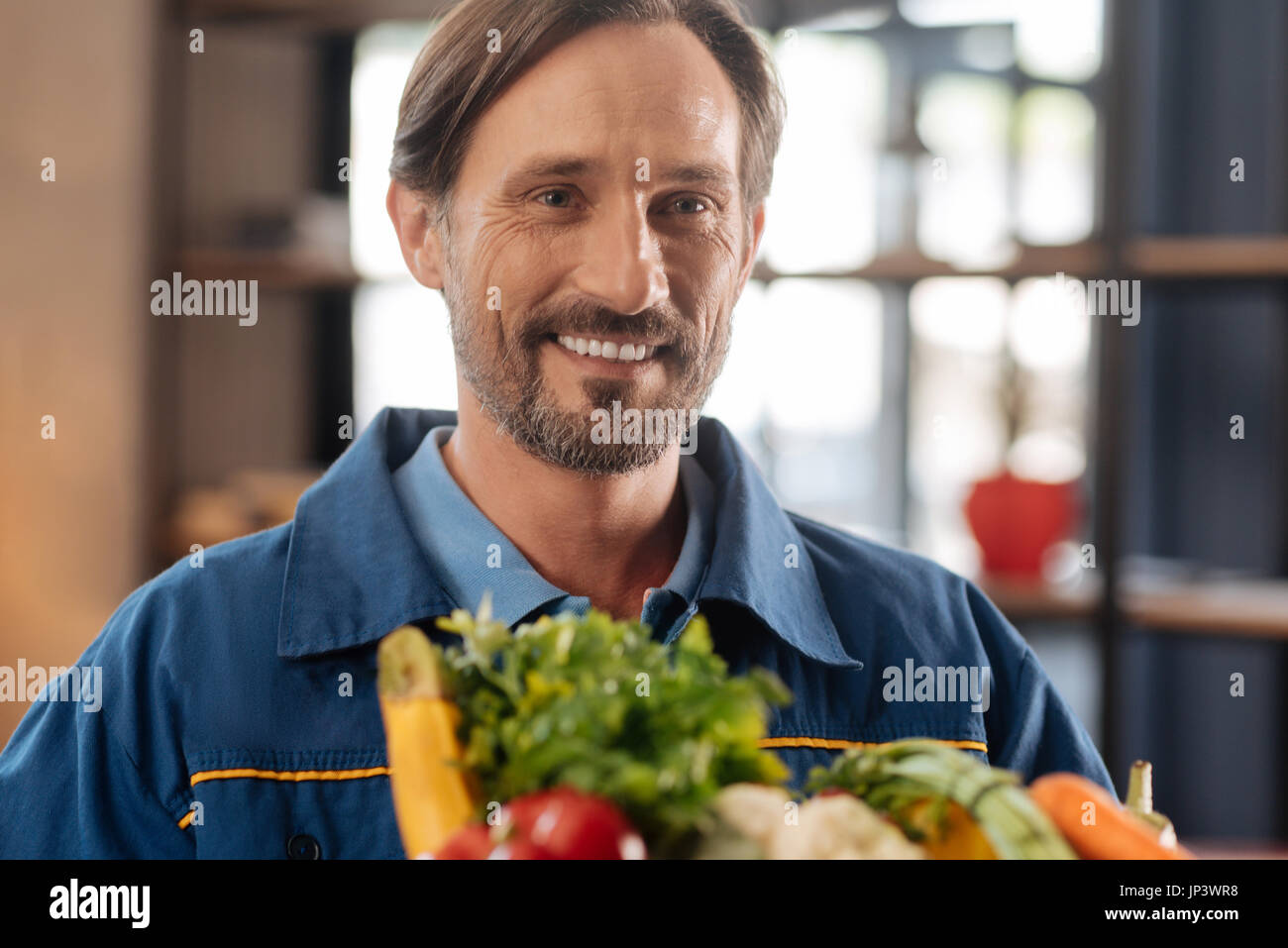 Picture of handsome positive deliveryman - Stock Image
