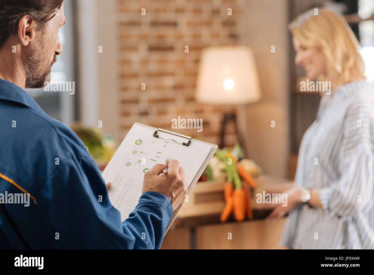 Attentive professional courier checking delivery list Stock Photo