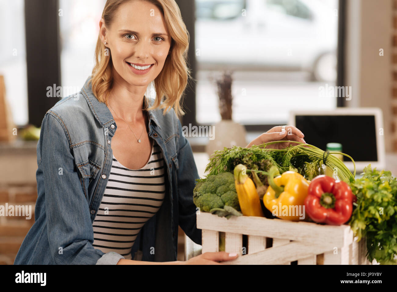 Gorgeous clever woman storing vegetables in special box - Stock Image
