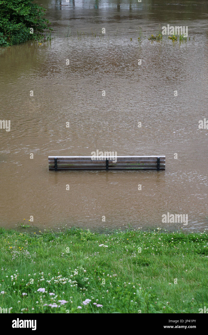 river flood with flooded park bench Stock Photo