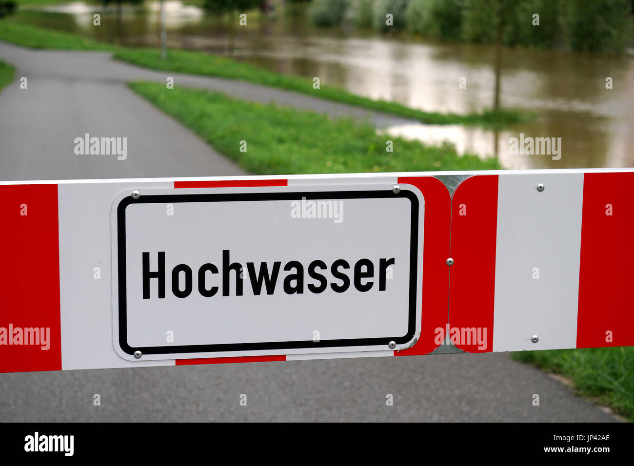 road blocked due to flooding, sign reads high water in German - Stock Image