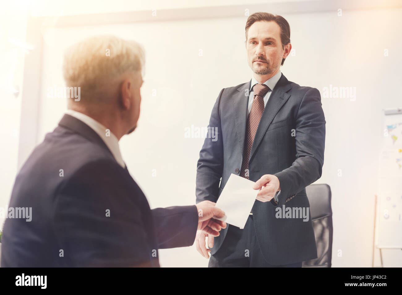 Determined ambitious man submitting his letter of resignation - Stock Image