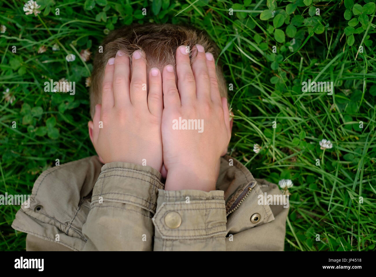 Teenage boy closes his eyes with hands - Stock Image