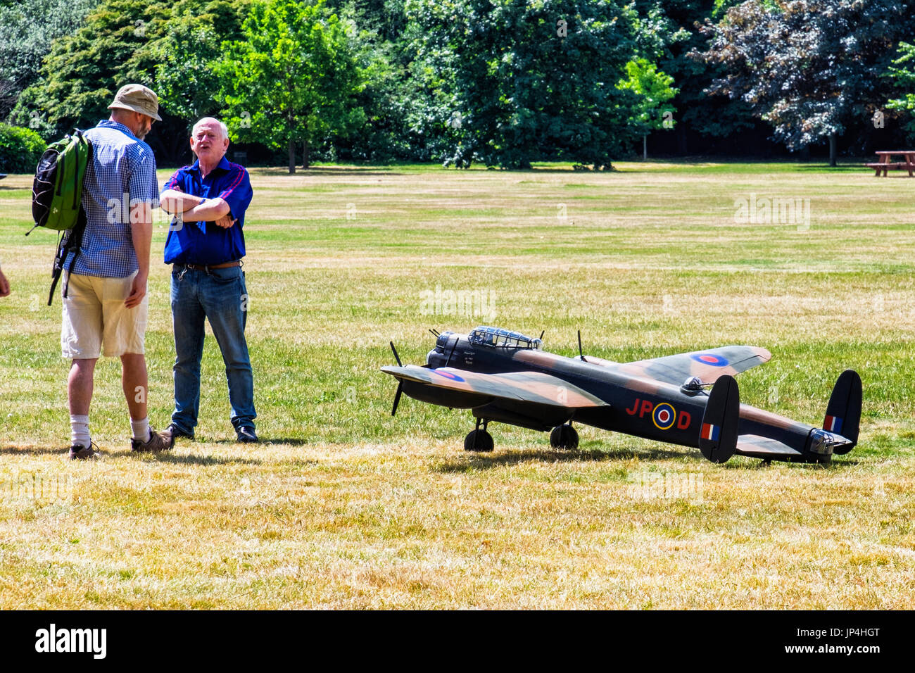 London,Greenwich Park. Two men standing next to model military aeroplane with camouflage paint work, Two men taking Stock Photo