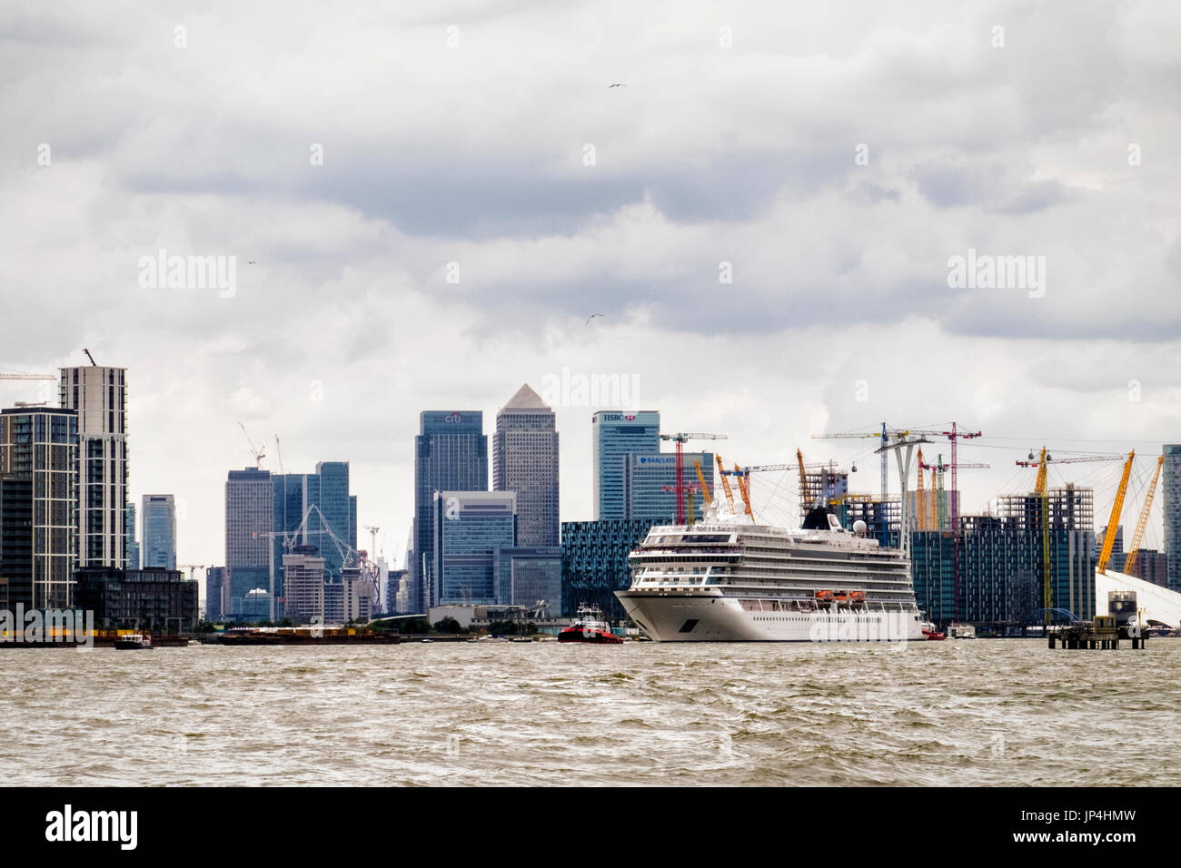 UK,London,MV Viking Sea cruise ship passes Canary Wharf banking and Financial centre as it leaves the city. Cruise liner leaves London. River Thames - Stock Image