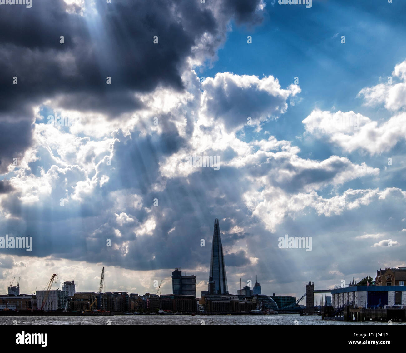 London,Uk.London skyline with sun shining through black cloudy sky. Rays of light, the Shard,dark clouds. - Stock Image