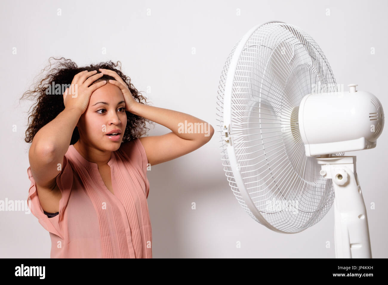Black woman feeling hot and sitting in front of an electric fan - Stock Image