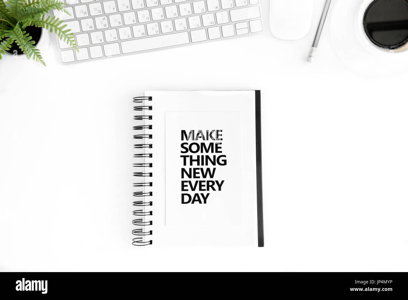 top view of make something new every day motivational quote in diary, computer mouse and keyboard isolated on white - Stock Image