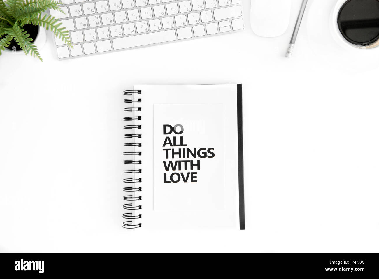 flat lay with do all things with love motivational quote in diary, computer mouse and keyboard isolated on white - Stock Image
