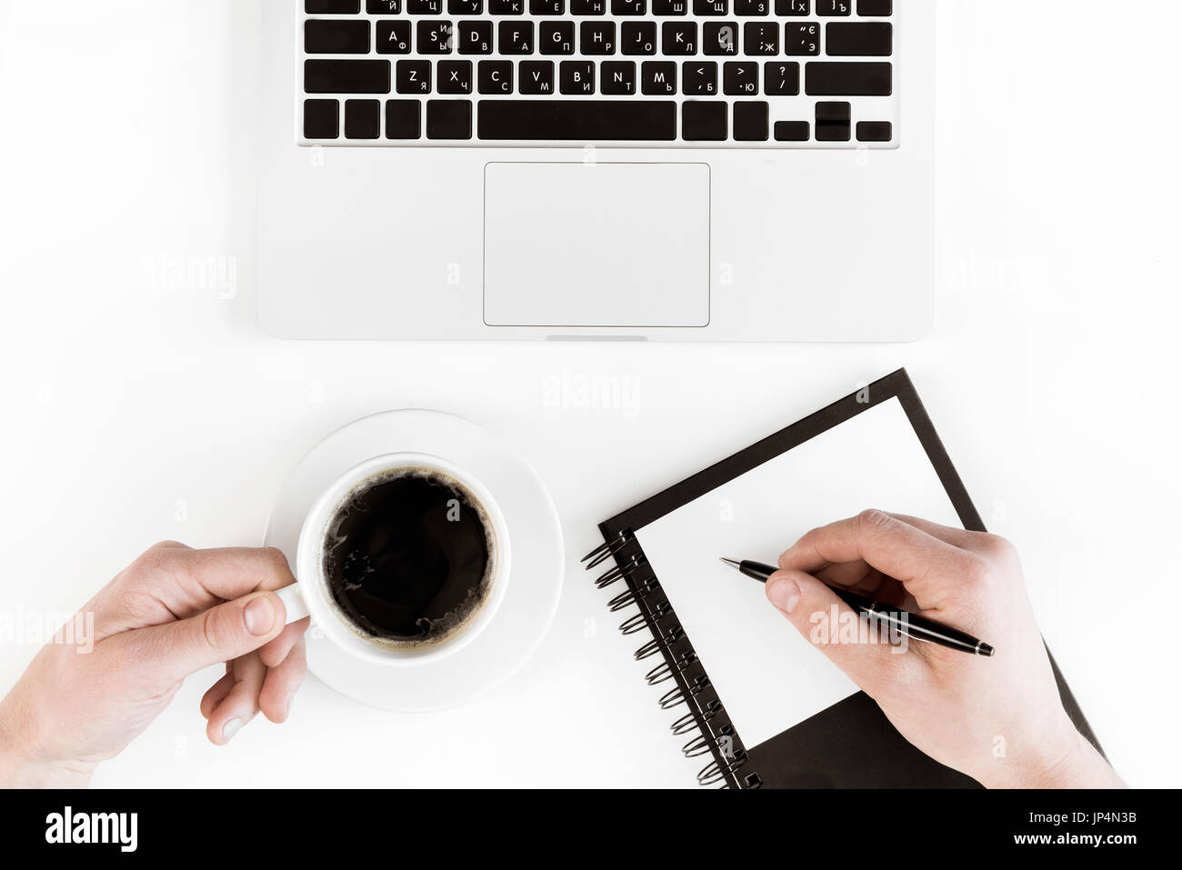 Partial top view of person holding cup of coffee and writing on blank paper at workplace with laptop, wireless communication concept - Stock Image