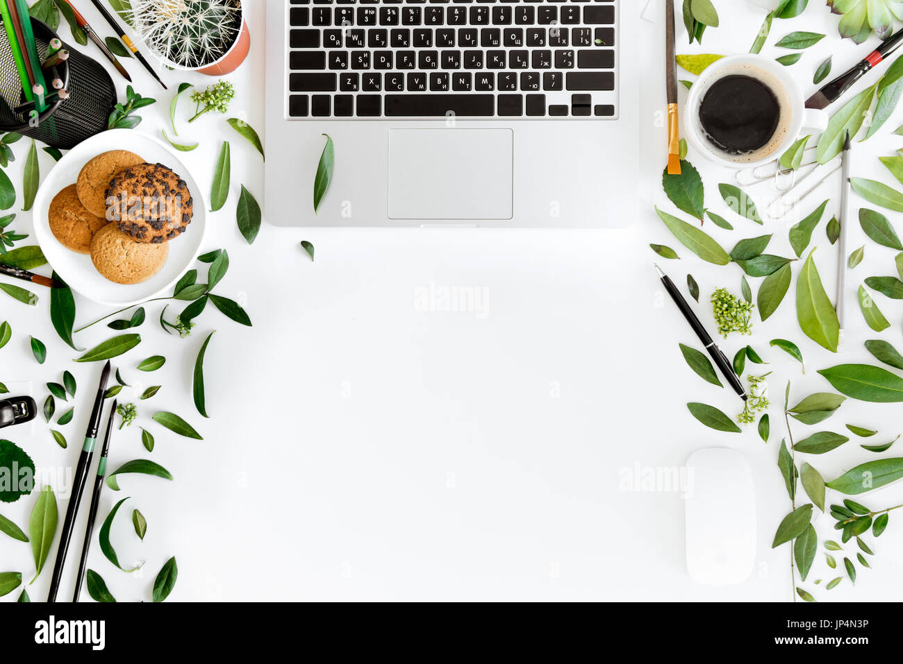 Top view of laptop, office supplies and cup of coffee at workplace isolated on white, wireless communication concept - Stock Image