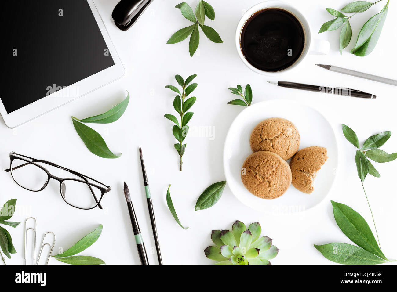 Top view of digital tablet, cookies and office supplies isolated on white, wireless communication concept - Stock Image