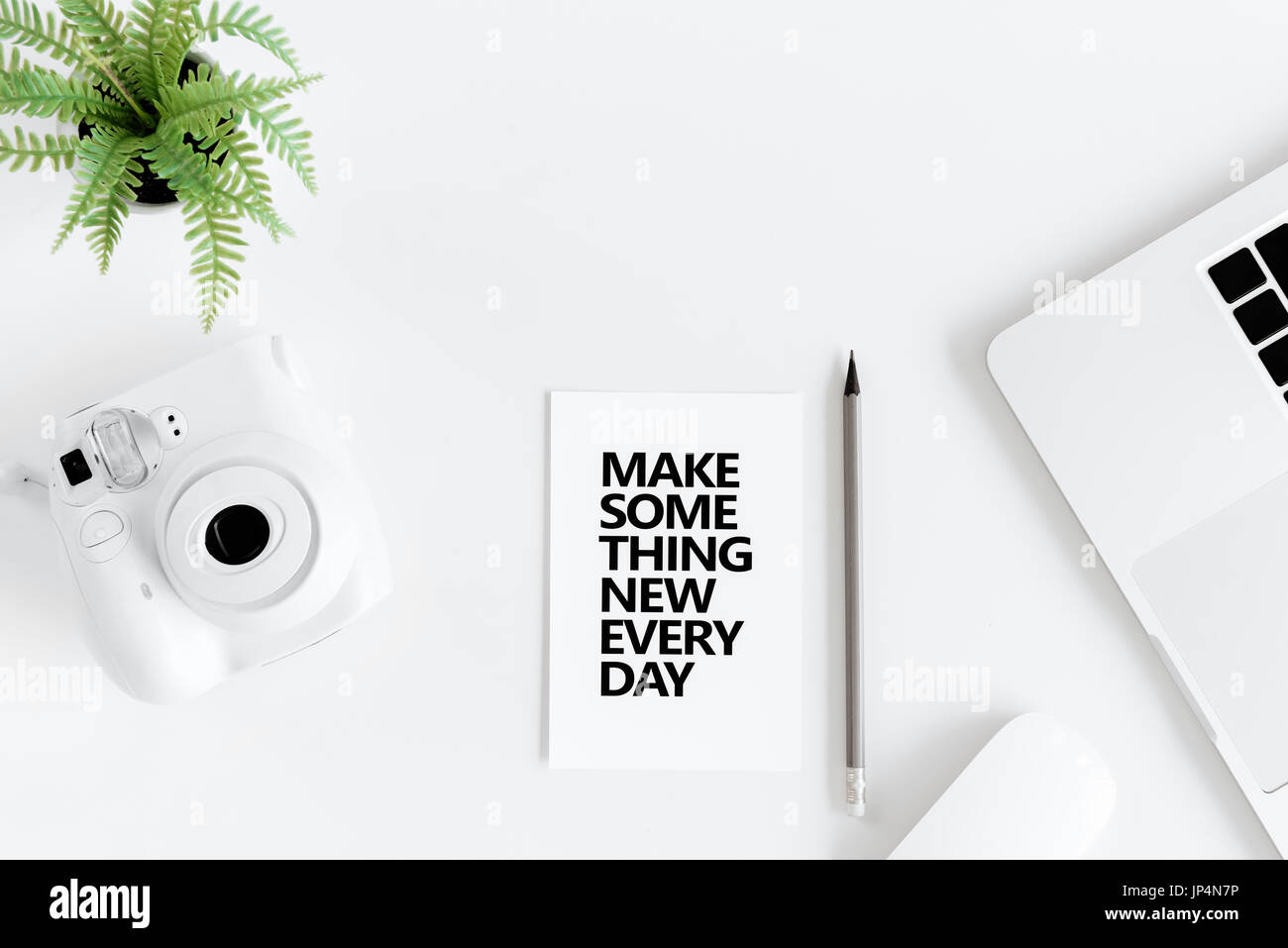 Top view of make something new everyday motivational quote and instant camera at workplace Stock Photo