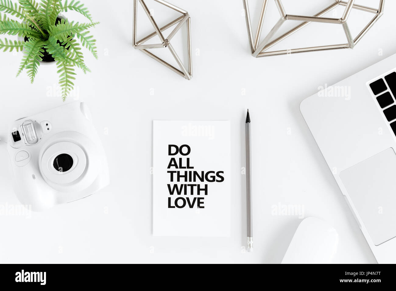 Top view of do all things with love motivational quote and instant camera at workplace - Stock Image