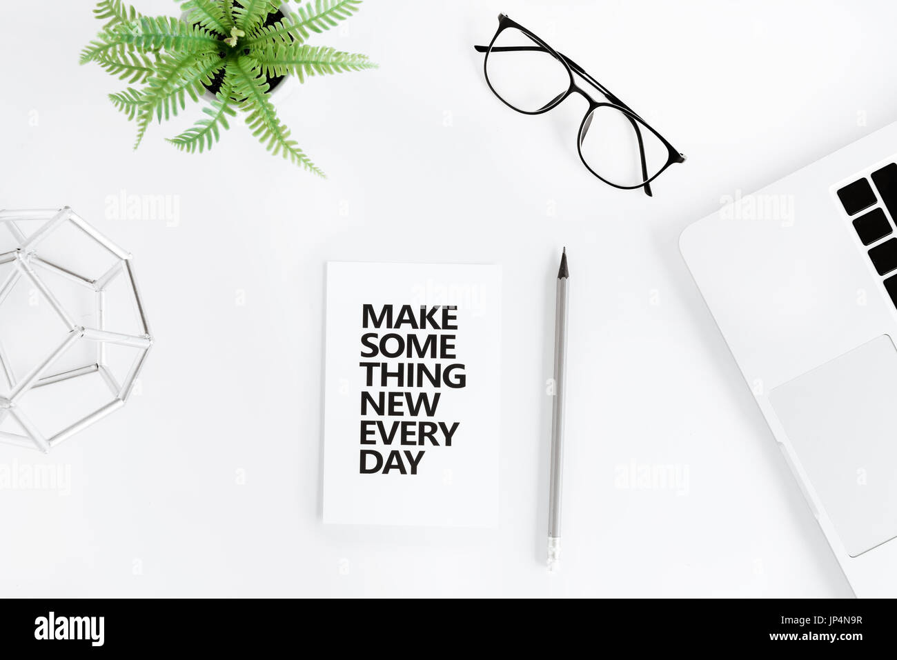 Top view of make something new everyday motivational quote and laptop at workplace - Stock Image