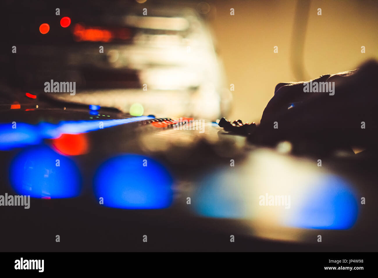 The hands of the sound engineer on the mixing console - Stock Image