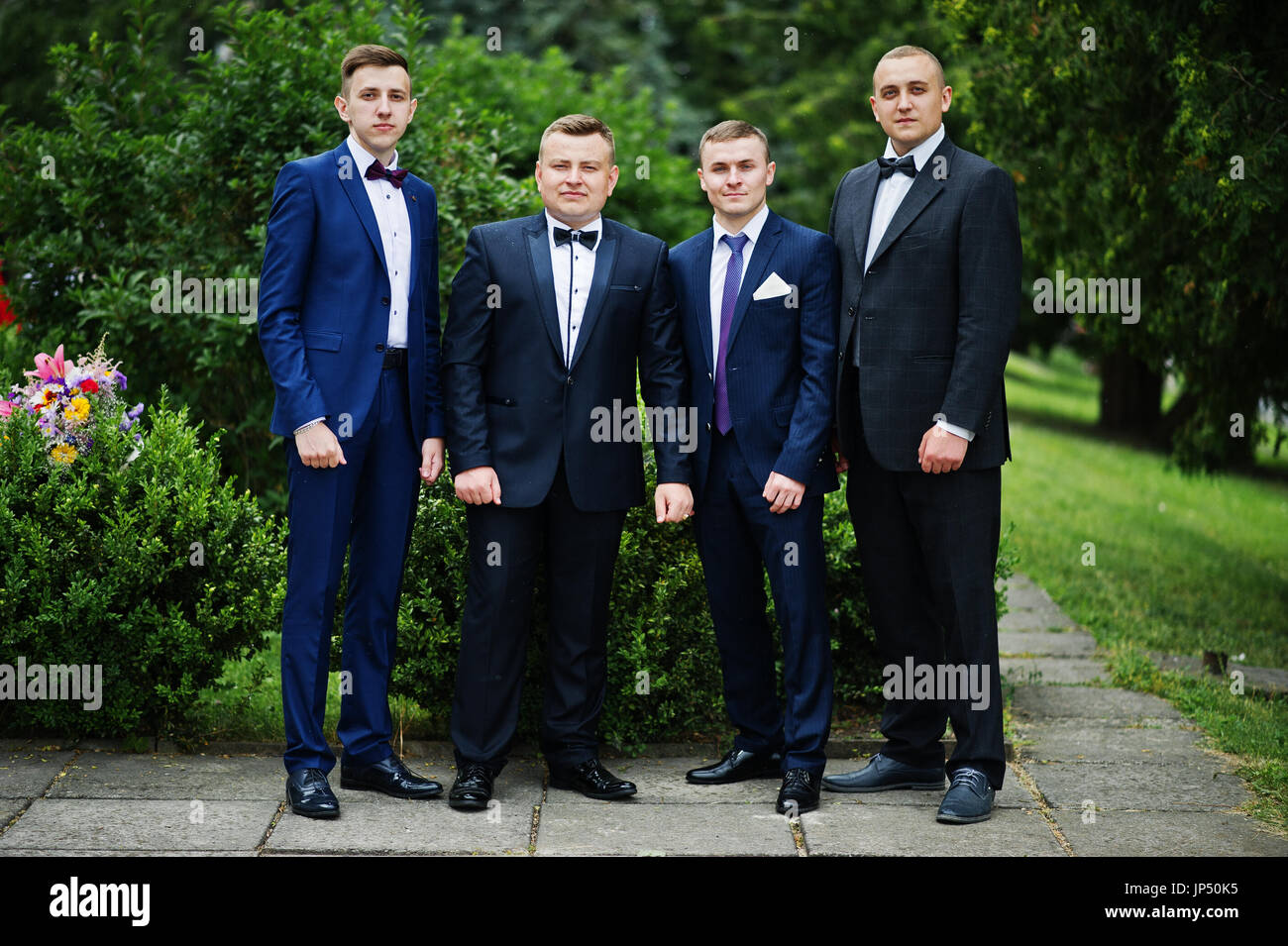 Four intelligent and handsome graduates in tuxedos posing on the graduation day. - Stock Image