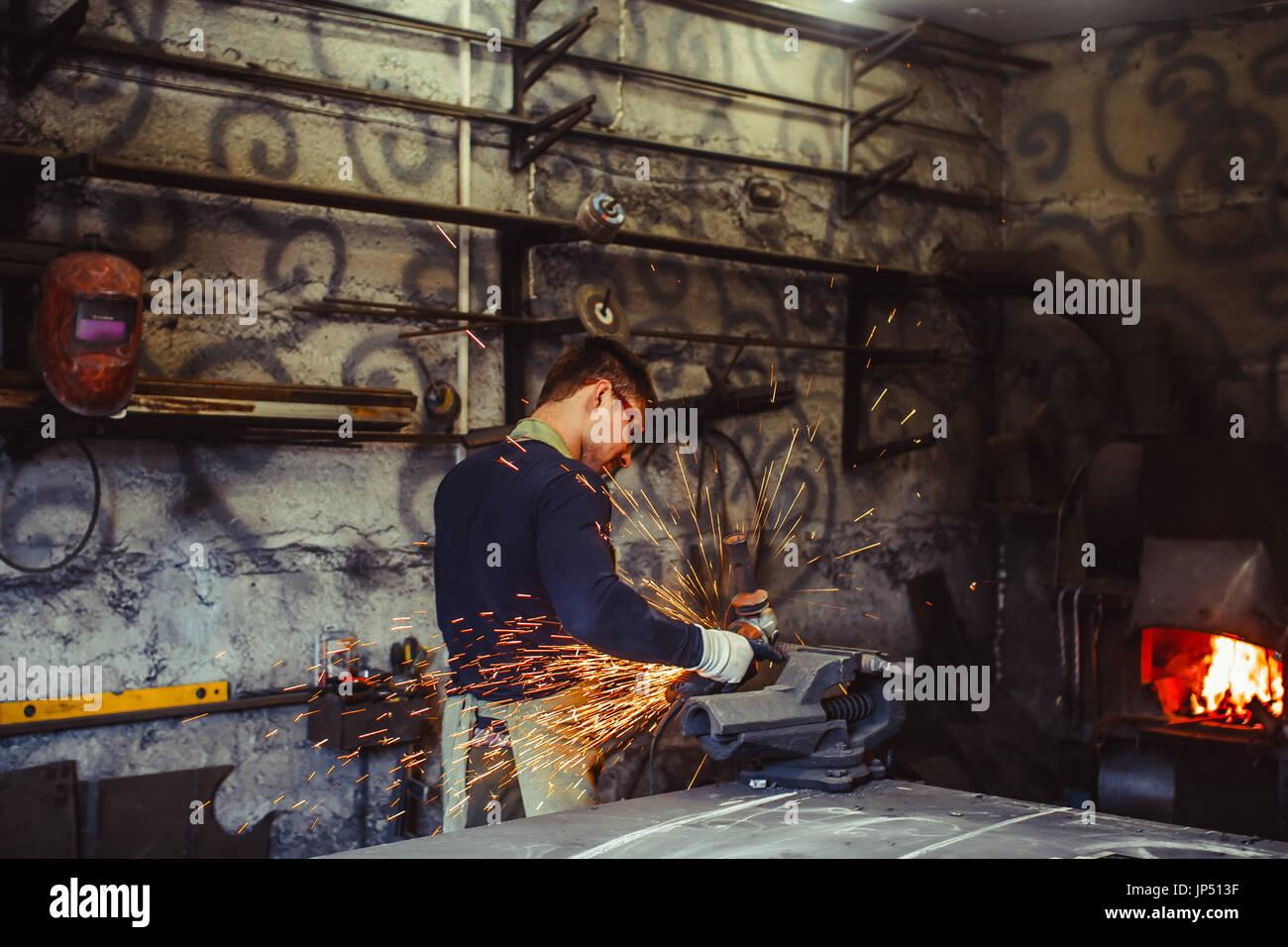 Craftsman sawing metal sparkles all around workshop. Working at noon. Stock Photo