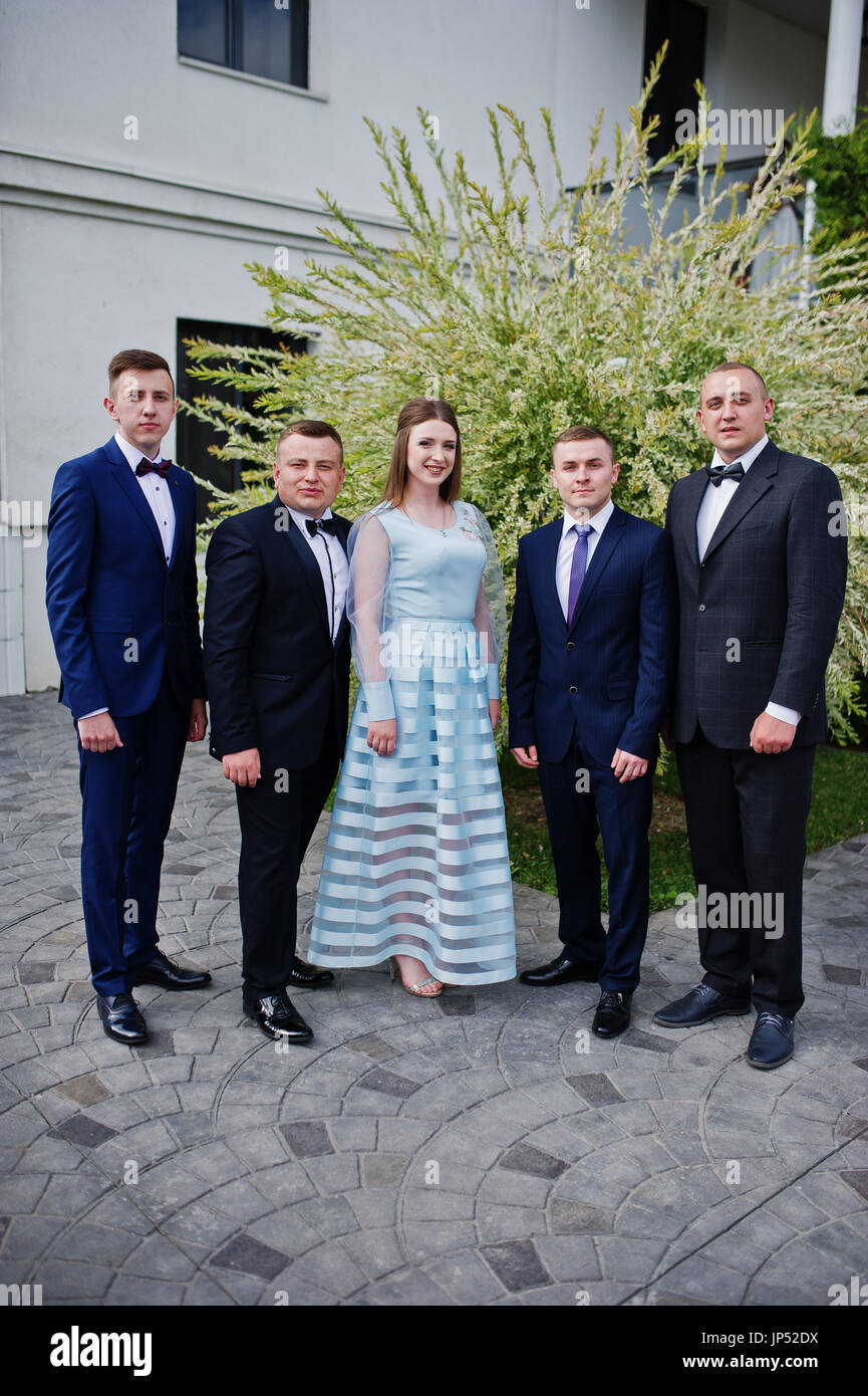 Beautiful girl in evening gown standing along with men in tuxedos on ...