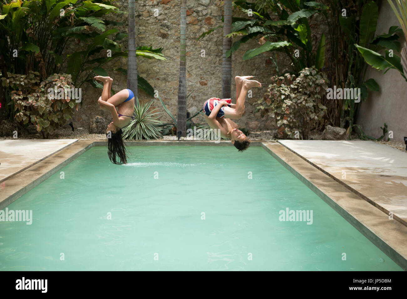 Two children in mid air, somersaulting backwards into a swimming pool. Stock Photo
