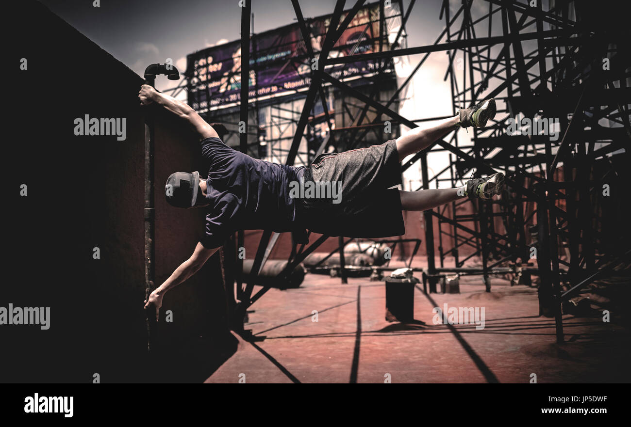 A parcour runner swinging from a scaffolding pole. - Stock Image