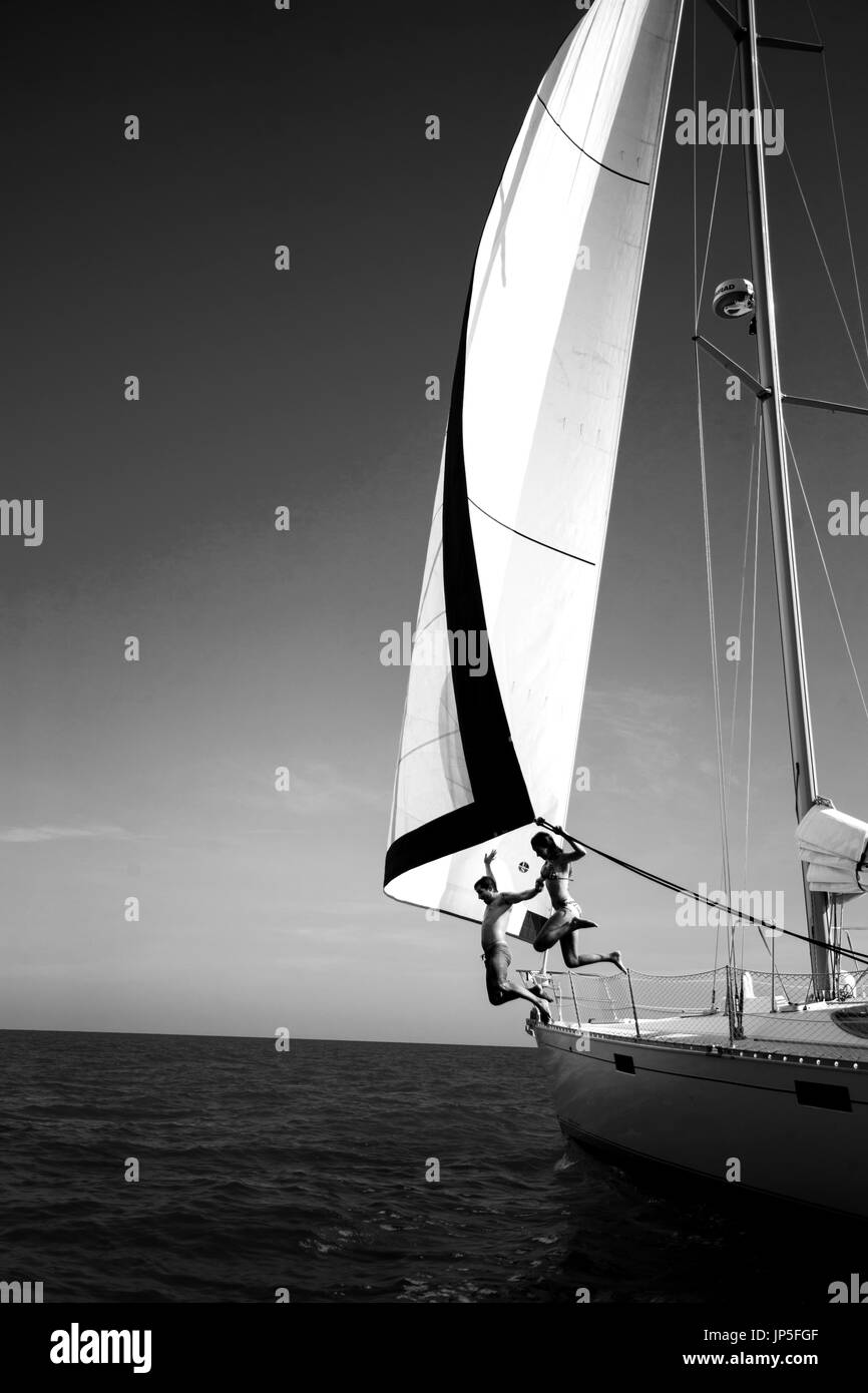 Two people jumping from a yacht into the ocean. - Stock Image
