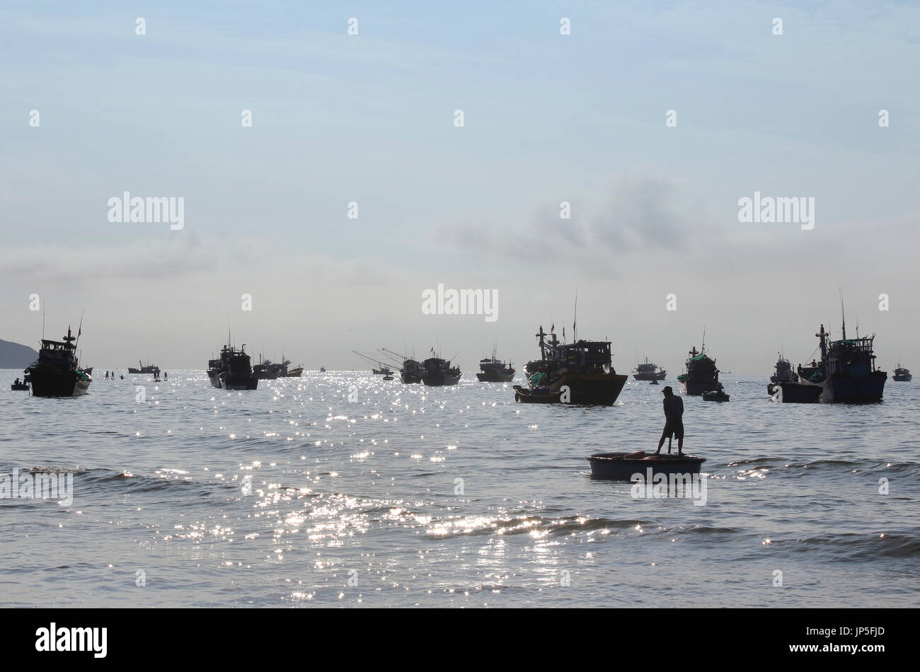 Morning view of Mui Ne fishing village with the Vietnamese rowing in round fishing boats - Stock Image