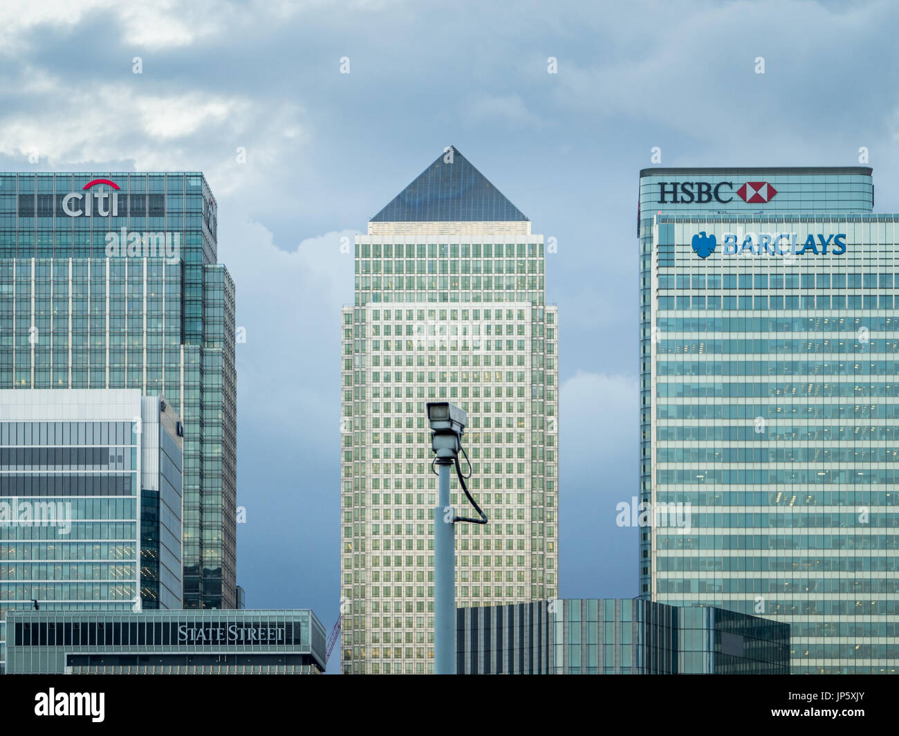 Canary Wharf, a major financial district in London, is seen from across the River Thames with a CCTV camera in the foreground. - Stock Image