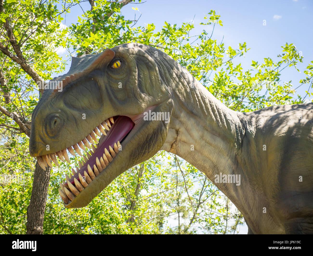 A life-sized model replica of a fearsome Tyrannosaurus rex at Prehistoric Park Calgary Zoo, Calgary, Alberta, Canada. - Stock Image