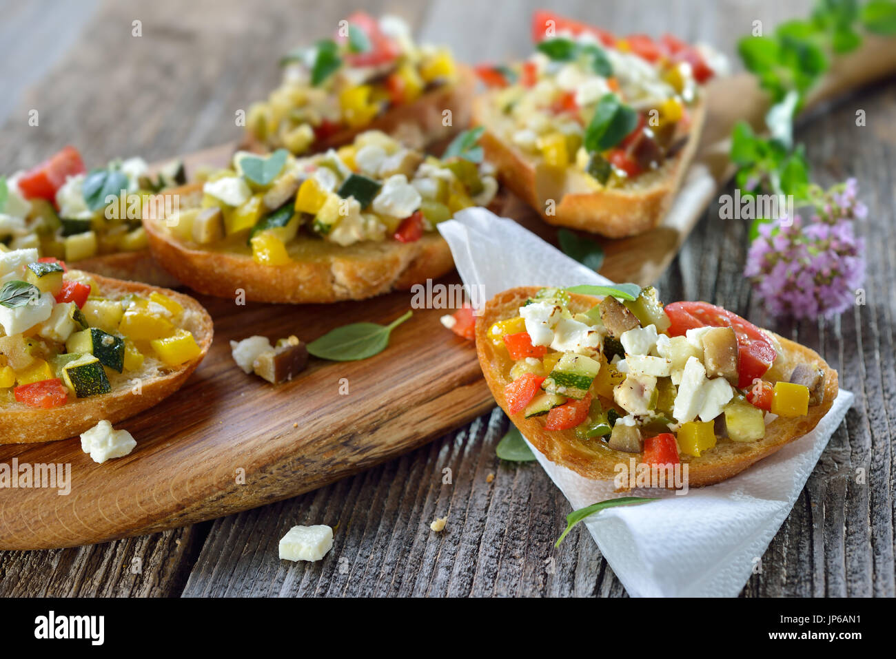 Warm vegetarian canapes: Baked crostini with mixed Greek vegetables with feta cheese served on a wooden cutting board - Stock Image