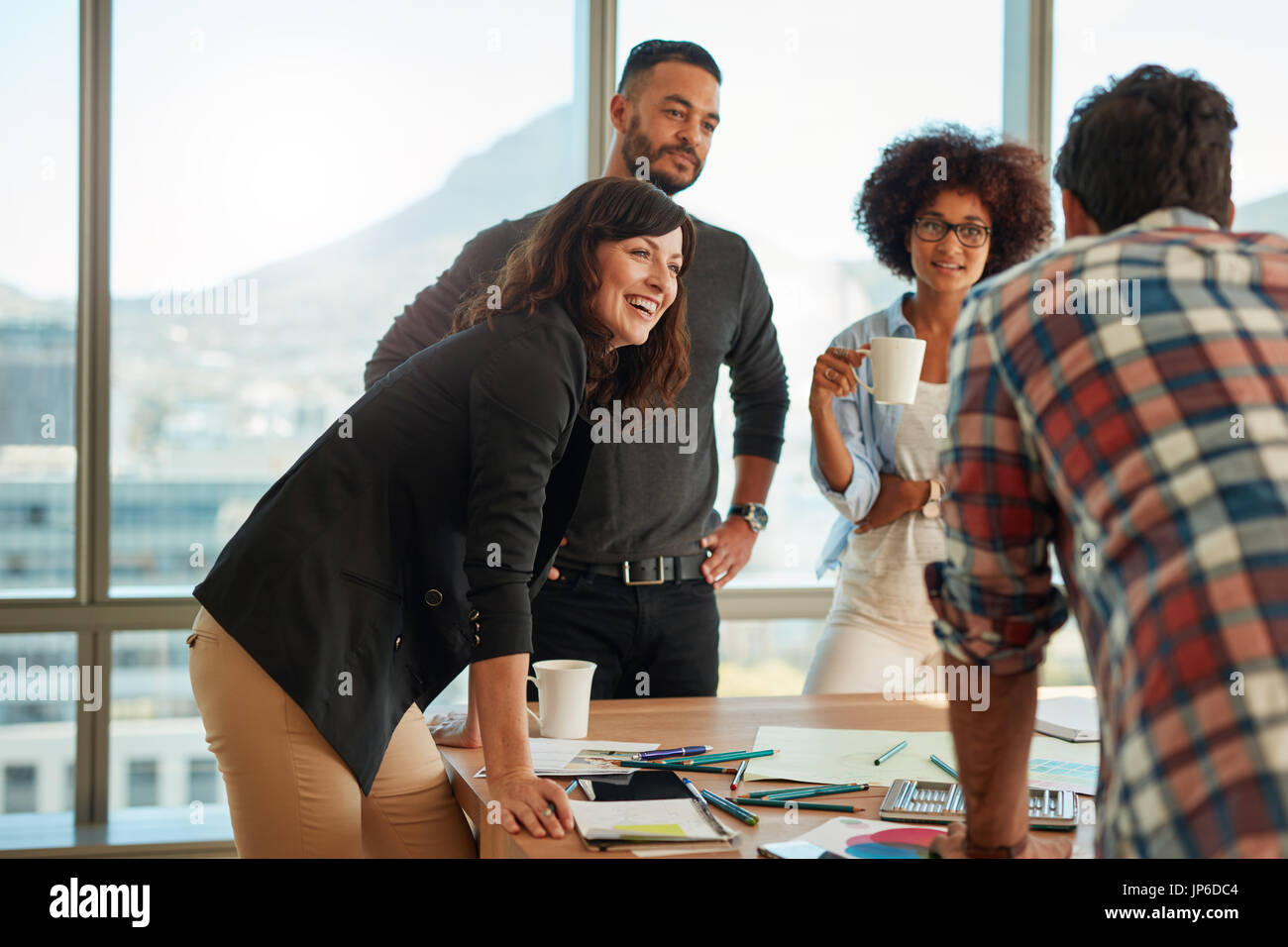 Young and creative team discussing ideas in board room. Group of multi ethnic people during business meeting. - Stock Image