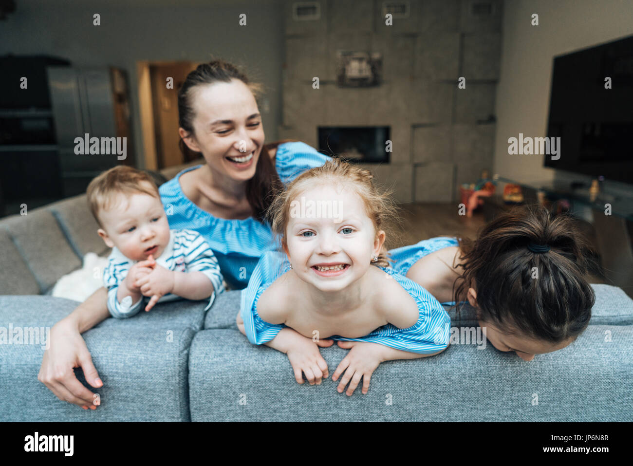 Mom, two daughters and a little son on the couch - Stock Image