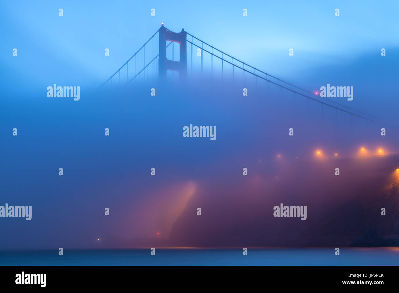 Nightfall as fog covered part of the Golden Gate Bridge in San Francisco, California. - Stock Image