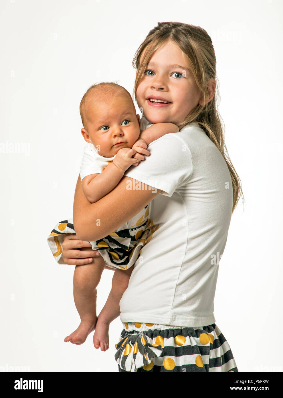 Studio portrait of 7 year old girl holding 7 week old baby - Stock Image