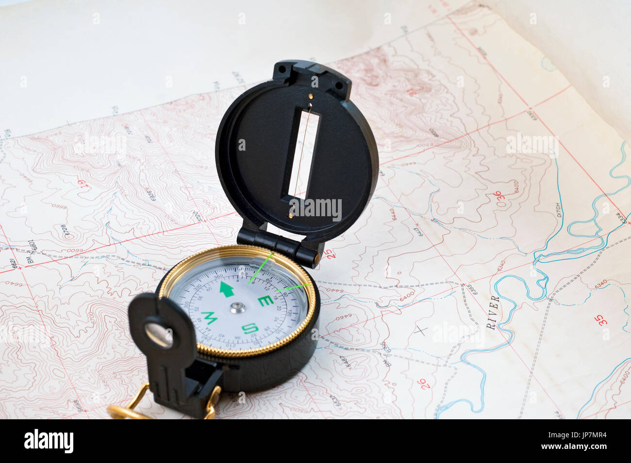 Compass sitting on a topo map. - Stock Image