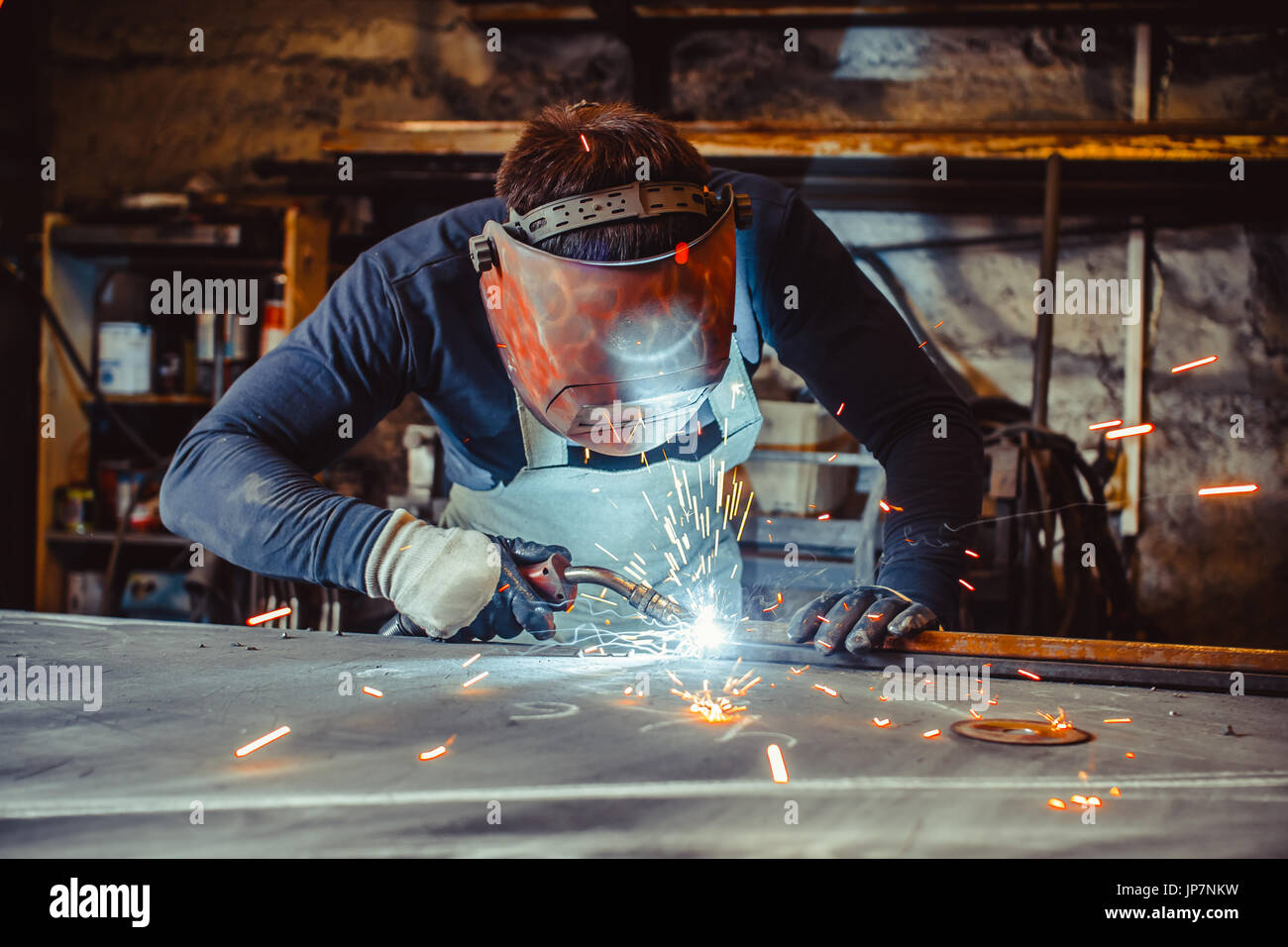 Young man with protective goggles welding in a factory - Stock Image