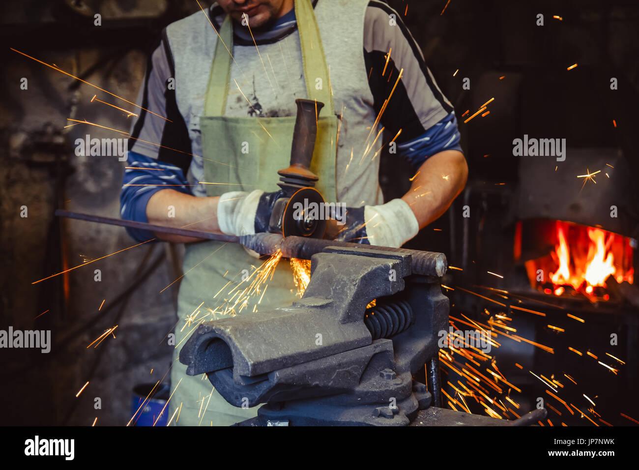 Craftsman sawing metal sparkles all around workshop. Working at noon. - Stock Image