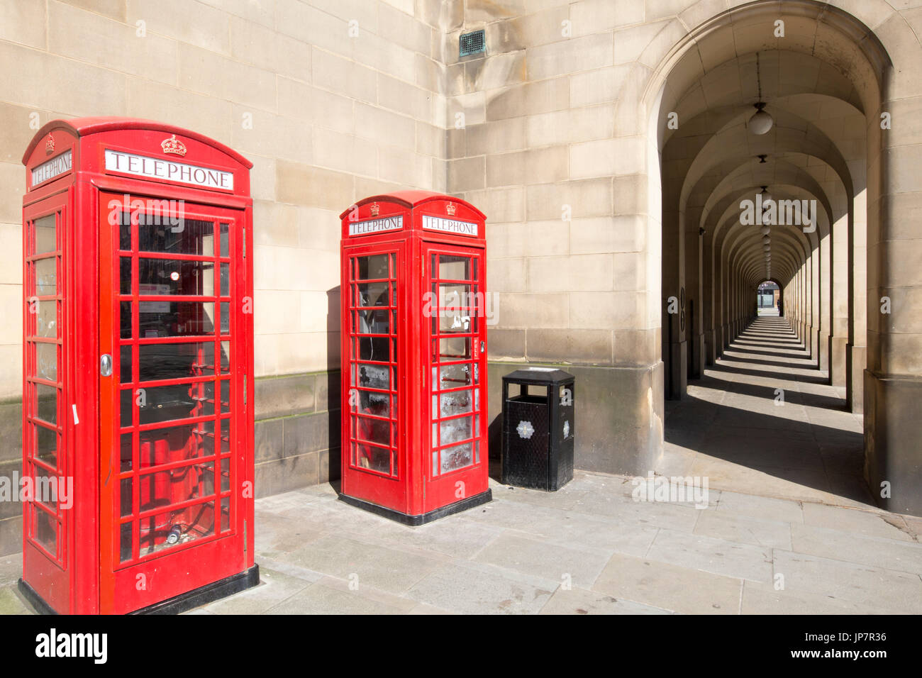 Classic British view in Manchester of old colonnades from the Manchester Town Hall Extension and iconic Red Phone Stock Photo