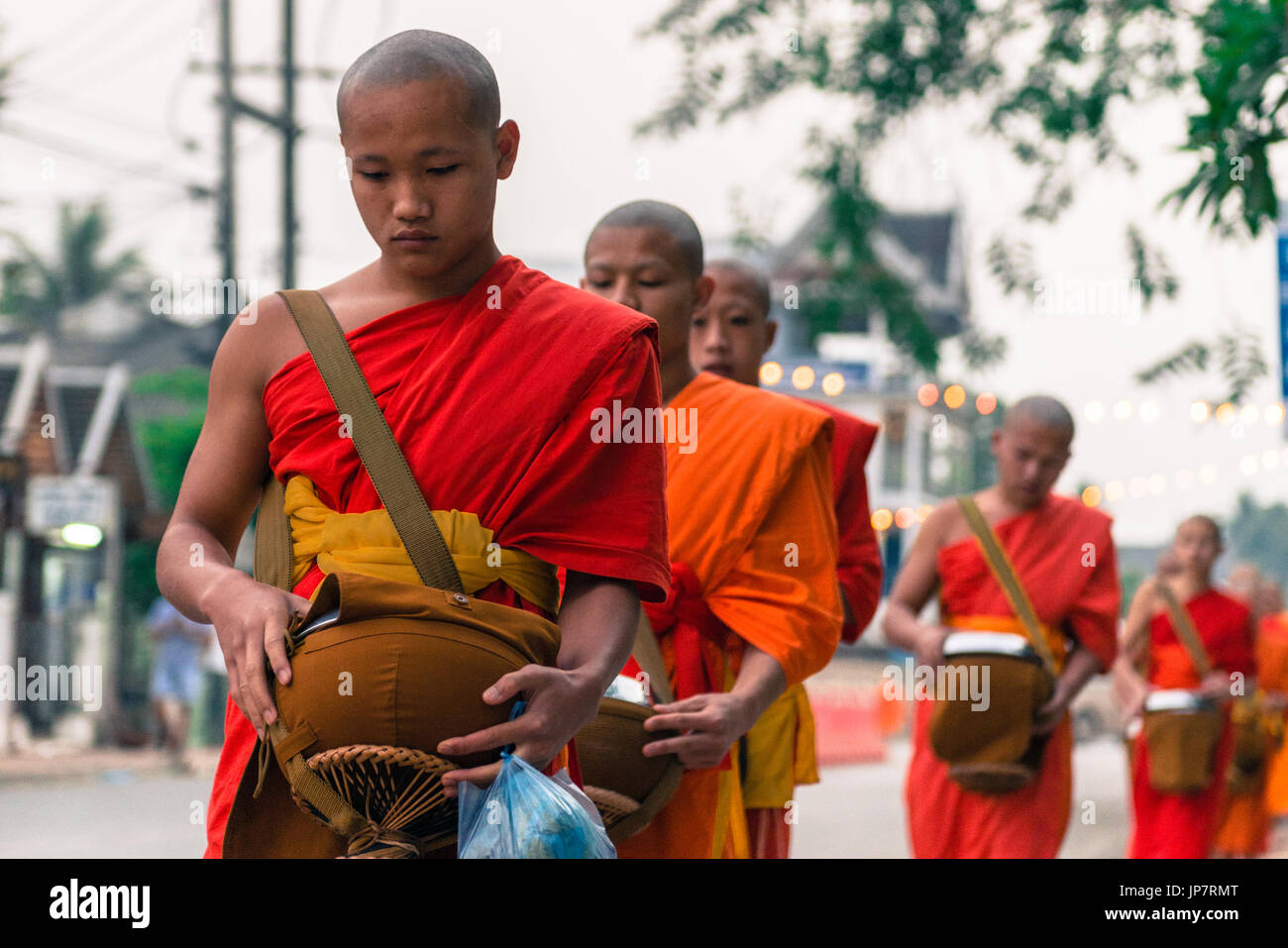 LUANG PRABANG, LAOS - MARCH 12, 2017: Horizontal picture of young monks going in line to Buddhist Alms Giving Ceremony, Stock Photo