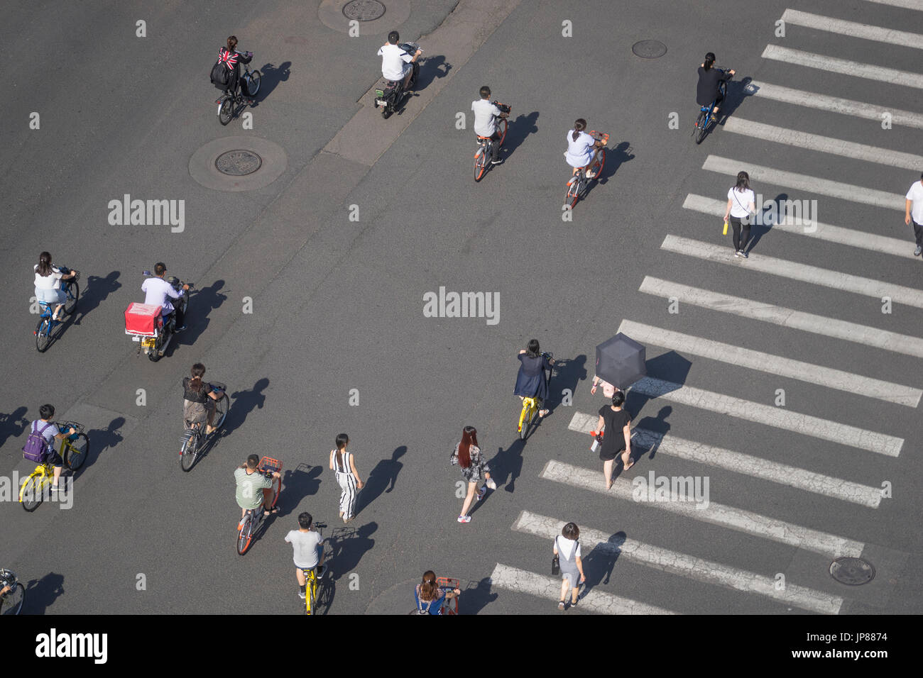 Pedestrians, cyclists and moped crossing street across a crosswalk while taxis wait walking across a wide city street with crosswalk - Stock Image