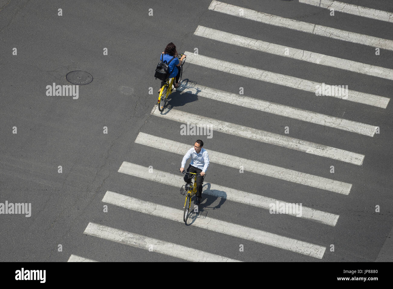 Aerial view of two people bicycling across the crosswalk of a wide road casting shadows on the lines - Stock Image