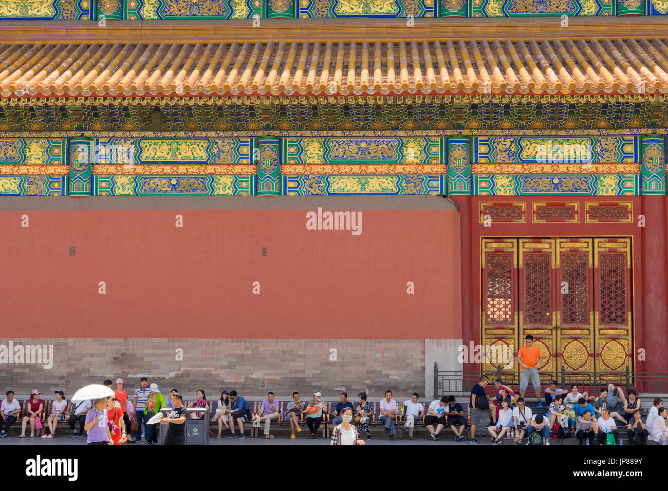 Chinese tourists sitting and taking a break from visiting Forbidden City - some eating some on their mobile phones and some talking - Stock Image