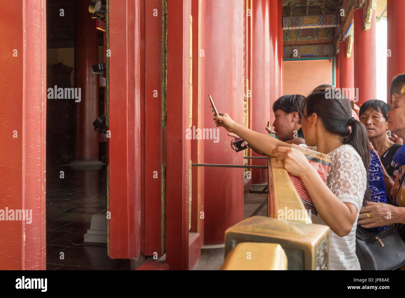 Chinese tourists clamboring to get a glimpse and take a mobile phone photo of the Hall of Supreme Harmony in the Forbidden City - Stock Image