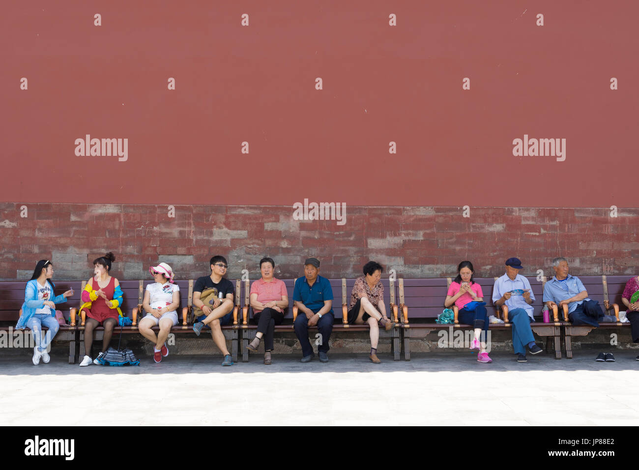 Chinese tourists of different ages sitting on bench at Forbidden City in Beijing - some resting, some talking, one on her mobile phone - Stock Image