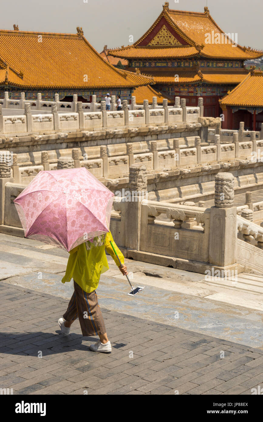 Woman holding shade umbrella and mobile phone with selfie stick walking by Palace of Heavenly Purity at Forbidden City in Beijing - Stock Image