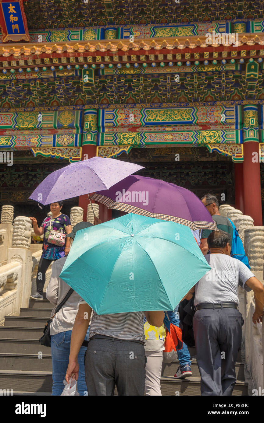 Tourists holding colorful shade umbrellas approaching the Hall of Supreme Harmony in the Forbidden City, Beijing, China - Stock Image
