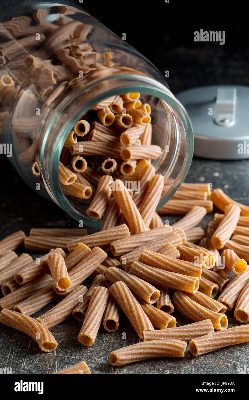 Dried rigatoni pasta in jar.  Dark semolina pasta. Uncooked pasta. - Stock Image