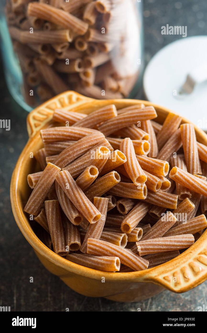 Dried rigatoni pasta in bowl. Dark semolina pasta. Uncooked pasta. - Stock Image