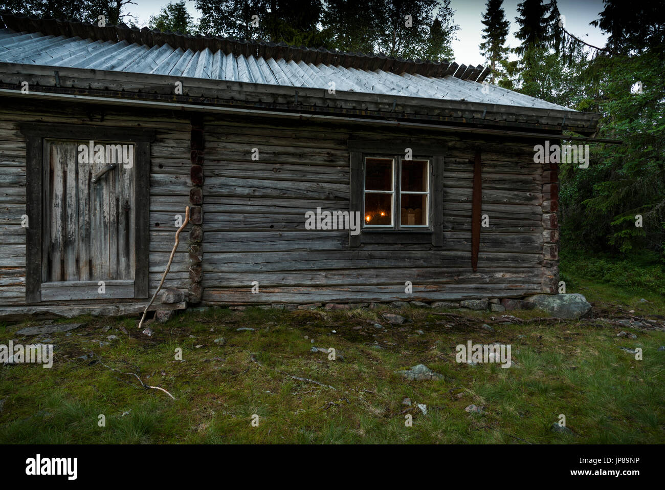 A lonely mountain hut in the forest in the nordic blue night. Two candles are lit inside. A wanderer's staff is resting against the wall. - Stock Image