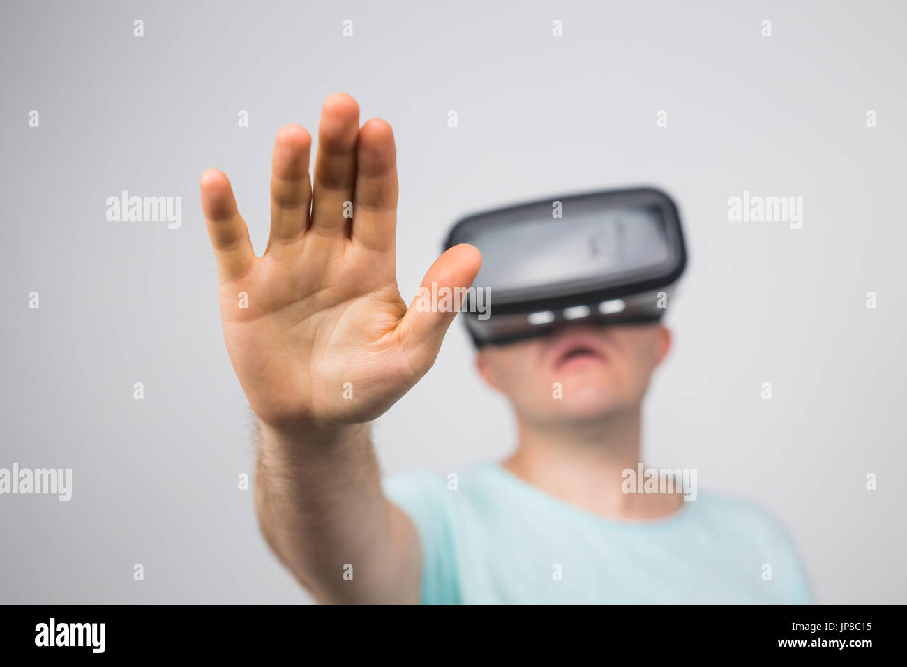 b5aaa5bbdd8e Excited young man using a VR headset and experiencing virtual reality  isolated on gray background